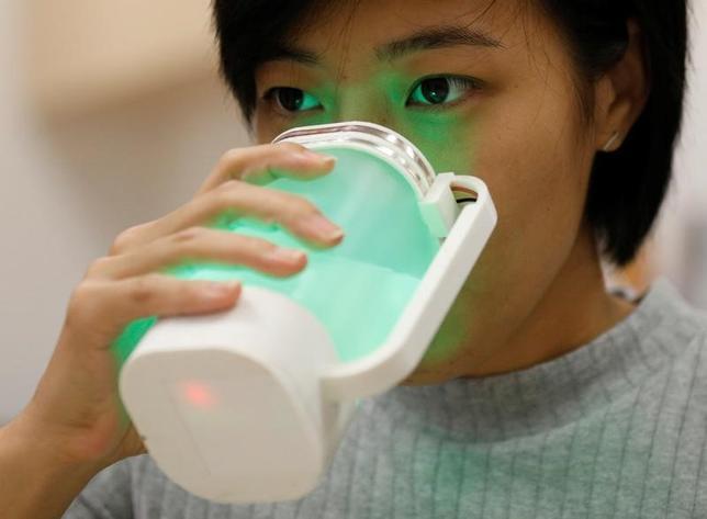 4月21日、シンガポール国立大学の研究チームが、電極とセンサーを利用して、水をレモネードそっくりに変えるプロジェクトに取り組んでいる。写真は13日撮影で、「仮想レモネード」を飲む学生(2017年 ロイター/Edgar Su)