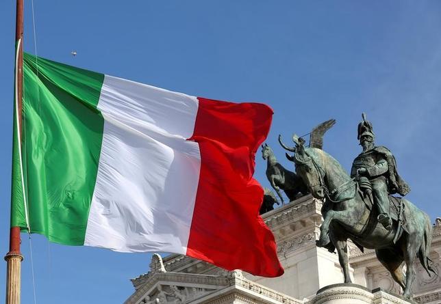 4月25日、仏大統領選はまだ最終結果が判明していないにもかかわらず、投資家は早くも来年のイタリア総選挙に関心を移し、より大きなリスクを市場にもたらしかねないと警戒している。写真は、イタリア国旗とヴィットーリオ・エマヌエーレ2世記念堂。ローマで昨年3月撮影(2017年 ロイター/Stefano Rellandini)
