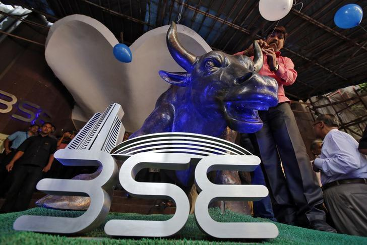 A man ties a balloon to the horns of a bull statue at the entrance of the Bombay Stock Exchange (BSE) while celebrating the Sensex index rising to over 30,000, in Mumbai, India April 26, 2017. REUTERS/Shailesh Andrade/File Photo