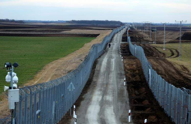 FILE PHOTO: A Hungarian policeman patrols the Hungary-Serbia border, which was recently fortified by a second fence, near the village of Gara, Hungary March 2, 2017. REUTERS/Laszlo Balogh