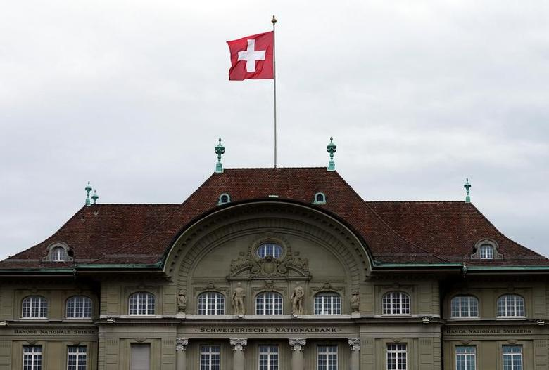 A Swiss national flag flutters in the wind atop the Swiss National Bank SNB headquarters in Bern, Switzerland April 16, 2015.  REUTERS/Ruben Sprich/File Photo