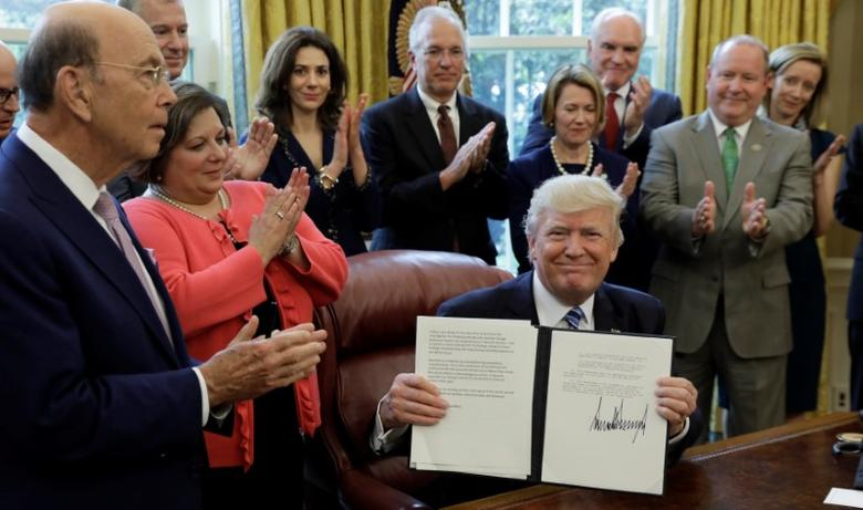 U.S. Commerce Secretary Wilbur Ross (L) and others applaud as U.S. President Donald Trump presents the signed Memorandum on Aluminum Imports and Threats to National Security at the White House in Washington, U.S., April 27, 2017.  REUTERS/Kevin Lamarque
