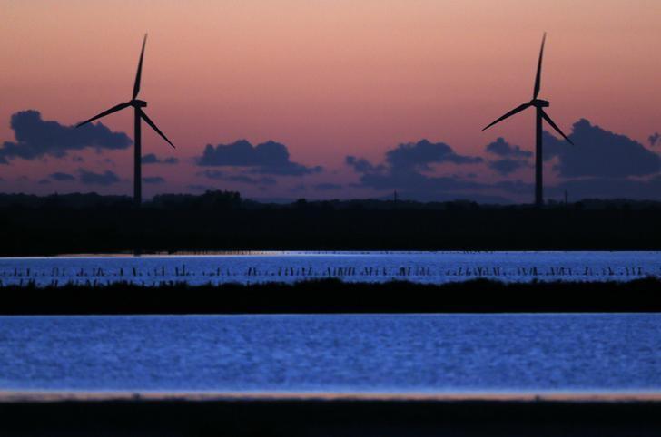 资料图片:2014年5月,法国马赛附近Saint Louis du Rhone港口旁暮色中的风力发电机。REUTERS/Jean-Paul Pelissier