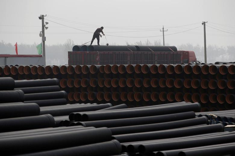 FILE PHOTO: A worker packs pipelines onto a truck at a local plastic pipe factory in Donghegang village on the outskirts of Xiongxian county, one part of the new special economic zone Xiong'an New Area, Hebei province, China, April 6, 2017.   REUTERS/Jason Lee/File Photo