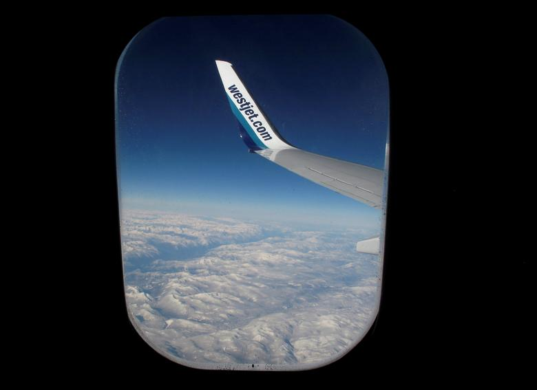 FILE PHOTO: Snow covered mountains are seen under the wing of a WestJet commercial flight on route from Vancouver to Calgary November 23, 2010.   REUTERS/Mike Blake/File Photo