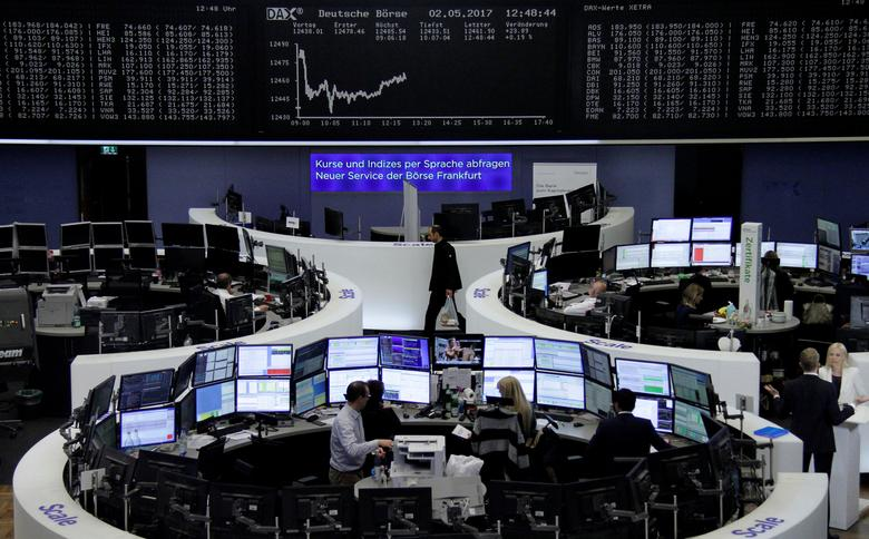 Traders work at their desks in front of the German share price index, DAX board, at the stock exchange in Frankfurt, Germany, May 2, 2017. REUTERS/Staff/Remote