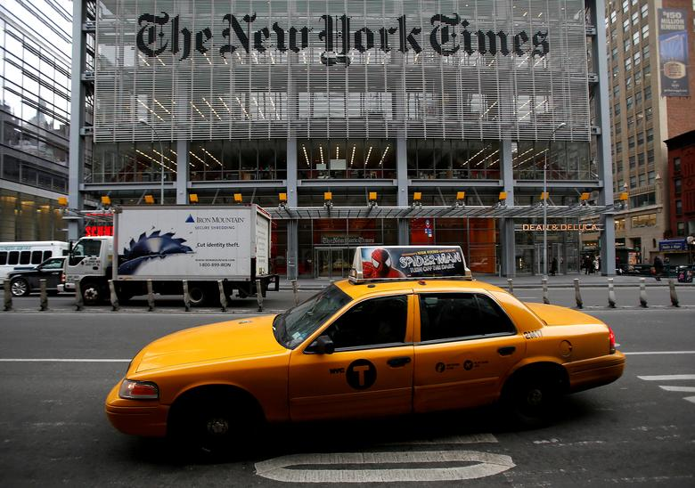 FILE PHOTO: A taxi passes by in front of The New York Times head office in New York, February 7, 2013.  REUTERS/Carlo Allegri/File Photo