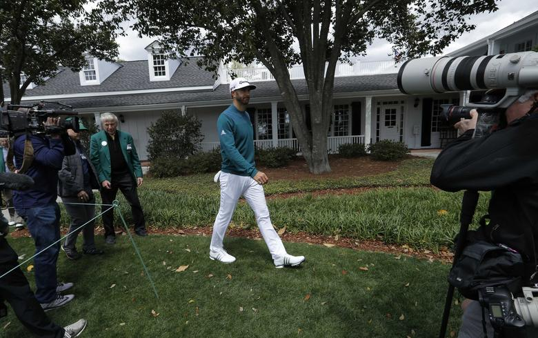 Dustin Johnson of the U.S. walks over to talk to members of the media after he pulled out of the tournament due to injury during first round play at the 2017 Masters golf tournament at Augusta National Golf Club in Augusta, Georgia, U.S., April 6, 2017. REUTERS/Mike Segar