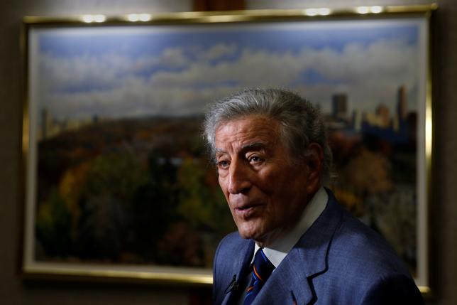 Singer and artist Tony Bennett speaks to a journalist in front of one his paintings before an opening of his art exhibition in the Manhattan borough of New York, U.S. May 3, 2017.   REUTERS/Carlo Allegri