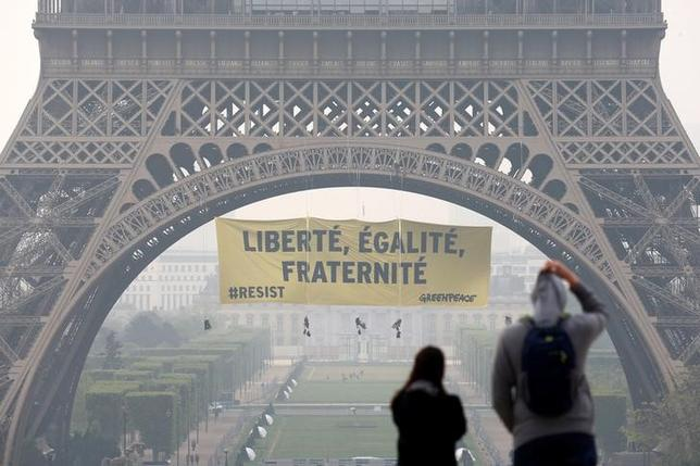 Tourists walk at Trocadero square as activists from the environmentalist group Greenpeace unfurl a giant banner on the Eiffel Tower which reads ''Liberty, Equality, Fraternity'' in a call on French citizens to vote against the National Front (FN) presidential candidate Marine Le Pen, in Paris, France May 5, 2017. REUTERS/Gonzalo Fuentes