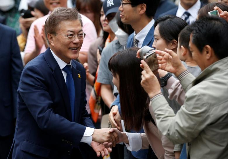Moon Jae-in, the presidential candidate of the Democratic Party of Korea, and his wife Kim Jung-sook (not pictured) greets supporters as they arrive at a polling station in Seoul, South Korea, May 9, 2017. REUTERS/Kim Kyung-Hoon