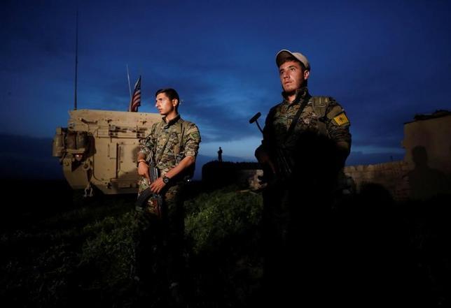 5月9日、トランプ米大統領は、シリアで過激派組織「イスラム国」(IS)と戦うクルド人武装組織「人民防衛隊」(YPG)に武器を供給することを承認した。写真は米国の軍用車のそばに立つYPG兵士。トルコのダルバシヤで4月撮影(2017年 ロイター/Rodi Said)