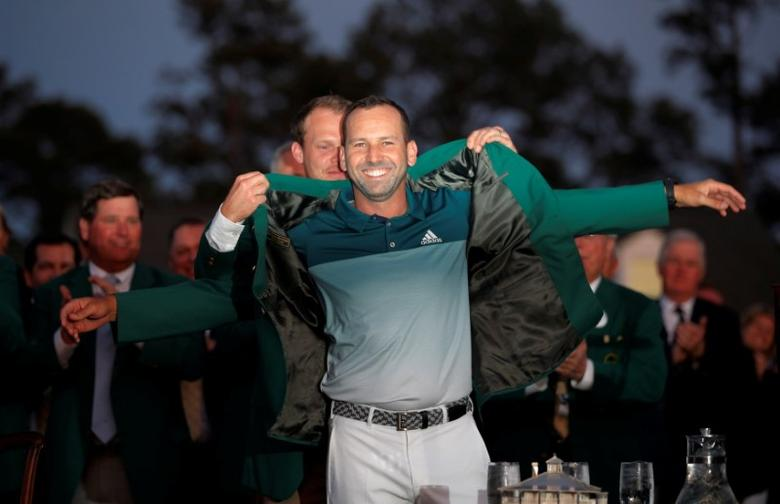 Sergio Garcia of Spain is presented the green jacket by last year's champion, Danny Willett of England, after Garcia won the 2017 Masters golf tournament in a playoff at Augusta National Golf Club in Augusta, Georgia, April 9, 2017. REUTERS/Brian Snyder