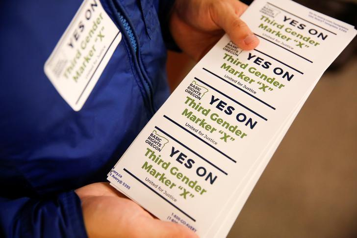 An employee of the advocacy group Basic Rights Oregon hands out stickers during an Oregon Driver and Motor Vehicle department public hearing on the rights of transgender people as the state considers adding a third gender choice to driver's licenses and identification cards, in Portland, Oregon, May 10, 2017. REUTERS/Terray Sylvester