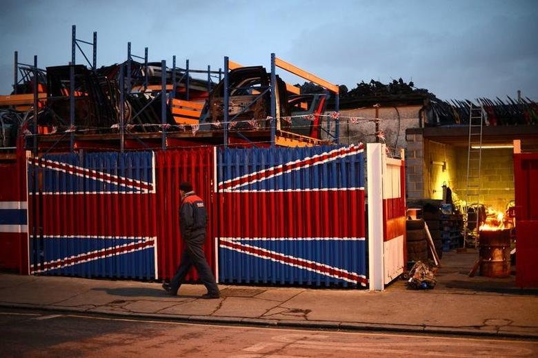 A man walks past a car scrap yard in east London January 25, 2013.   REUTERS/Paul Hackett/File Photo