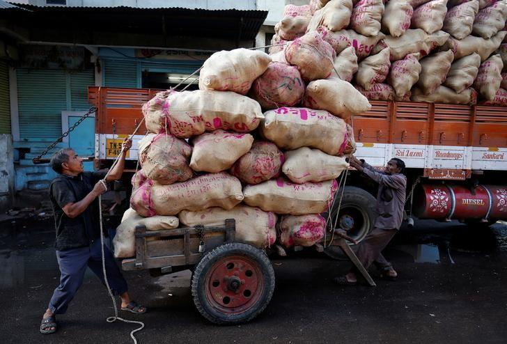 Labourers load sacks filled with coconuts on a hand cart at a wholesale market in Ahmedabad, India, March 14, 2017. REUTERS/Amit Dave/Files