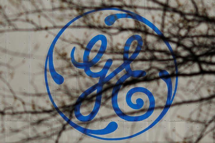 The logo of a General Electric (GE) facility is seen behind tree branches in Medford, Massachusetts, U.S., April 20, 2017.   REUTERS/Brian Snyder/Files