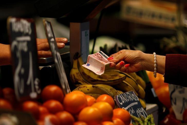 资料图片:2012年4月,西班牙Malaga,一名顾客在菜市场向摊贩付款。REUTERS/Jon Nazca/File Photo