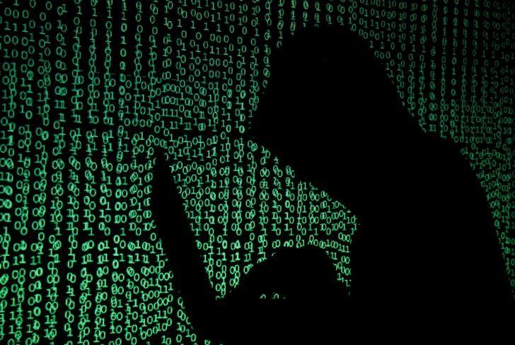 A hooded man holds a laptop computer as cyber code is projected on him in this illustration picture taken on May 13, 2017.  REUTERS/Kacper Pempel/Illustration/Files