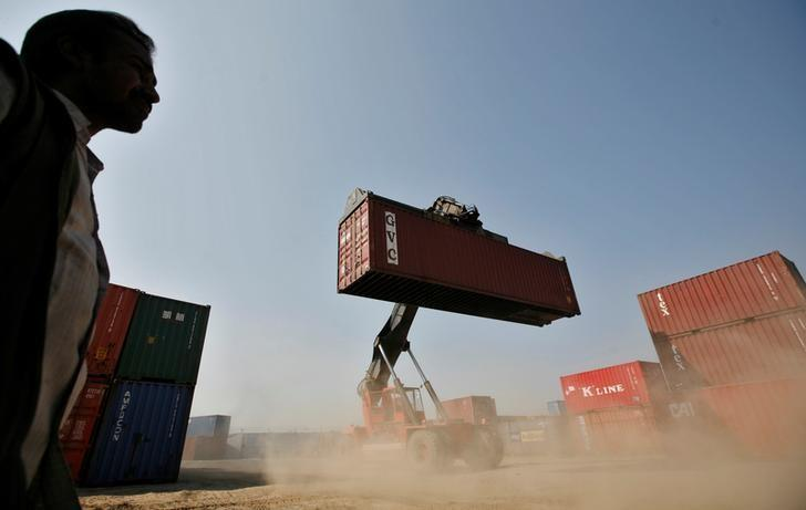 A worker prepares to stack a container at Thar Dry Port in Sanand in Gujarat, February 1, 2011.  REUTERS/Amit Dave/Files