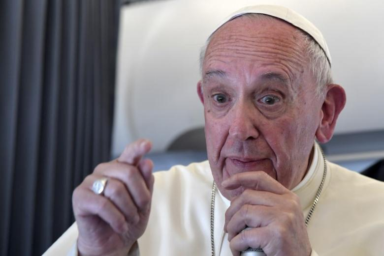 Pope Francis speaks to reporters as he flies back to Rome following the visit at the Holy Shrine of Fatima in Portugal May 13, 2017. REUTERS/Tiziana Fabi/Pool
