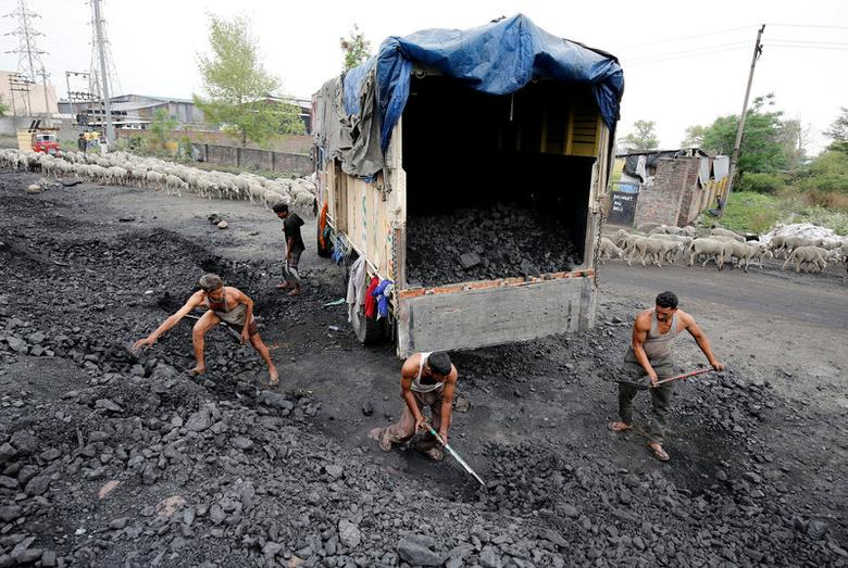 FILE PHOTO: Labourers load coal onto a supply truck on the outskirts of Jammu, India, April 6, 2017. REUTERS/Mukesh Gupta/File Photo