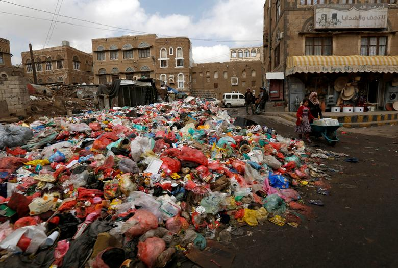 A girl pushes a wheel cart with water jerrycans past a pile of rubbish bags on a street during a strike by garbage collectors demanding delayed salaries in Sanaa. REUTERS/Khaled Abdullah