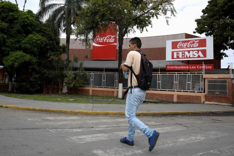 FILE PHOTO: A man walks next to corporate logos of Coca-Cola and Femsa at a distribution center of the company in Caracas, Venezuela May 24, 2016. REUTERS/Carlos Garcia Rawlins