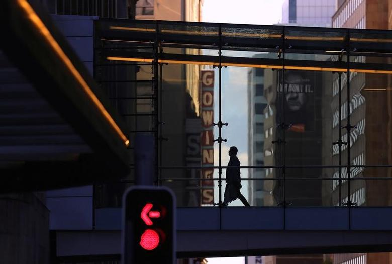 A shopper walks across a pedestrian bridge in the central business district (CBD) of Sydney, Australia, May 5, 2017. Picture taken May 5, 2017.      REUTERS/Steven Saphore