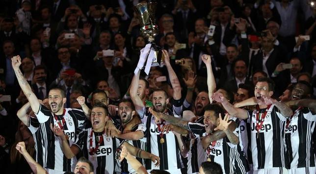 5月17日、サッカーのイタリア杯決勝、王者ユベントスがラツィオを2─0で下して3連覇を果たした。写真は優勝トロフィーを掲げるユベントスの選手たち(2017年 ロイター/Stefano Rellandini)