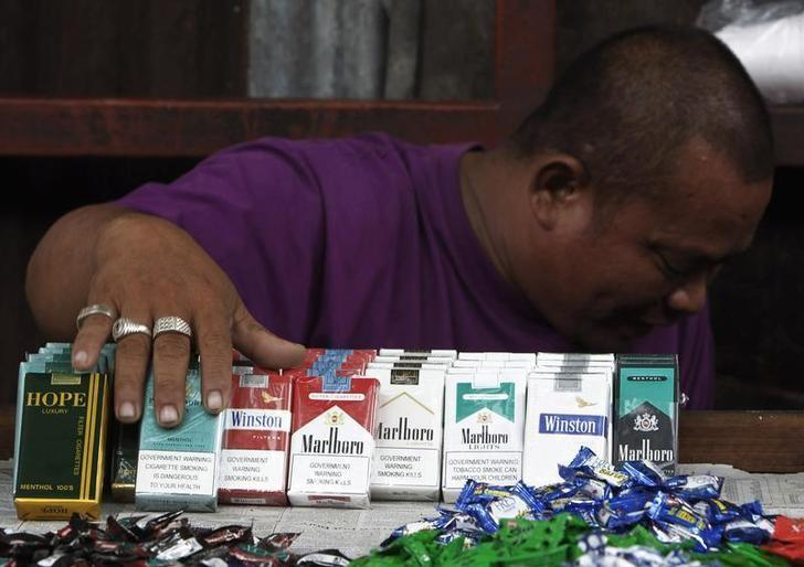 A vendor displays cigarettes as he waits for customers along a busy street in Manila May 30, 2011. REUTERS/Romeo Ranoco/Files