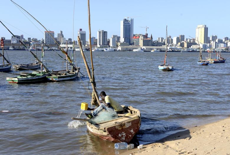 FILE PHOTO: A fisherman cleans his boat beneath Maputo's skyline, in this picture taken August 15, 2015. REUTERS/Grant Lee Neuenburg/File Photo