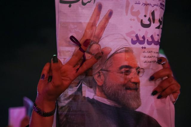 A supporter of Iranian president Hassan Rouhani holds his poster as she celebrates his victory in the presidential election, in Tehran, Iran, May 20, 2017. TIMA via REUTERS