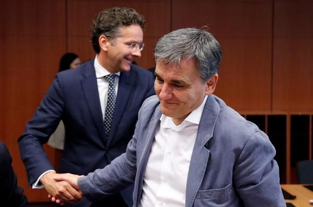 5月22日、ユーロ圏財務相会合(ユーログループ)では、ユーロ圏財務相、国際通貨基金(IMF)、ギリシャ政府が、ギリシャへの追加融資や同国の債務軽減を巡り合意できなかった。写真はデイセルブルム議長(左)と握手を交わすギリシャのチャカロトス財務相、ブリュッセルで撮影(2017年 ロイター/Francois Lenoir)