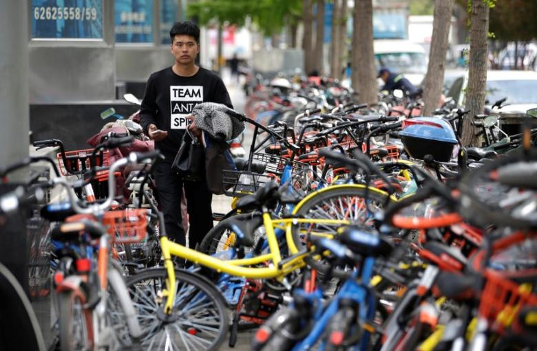 A man looks for a shared bike to ride outside an office building, in Beijing, China April 12, 2017.  REUTERS/Jason Lee