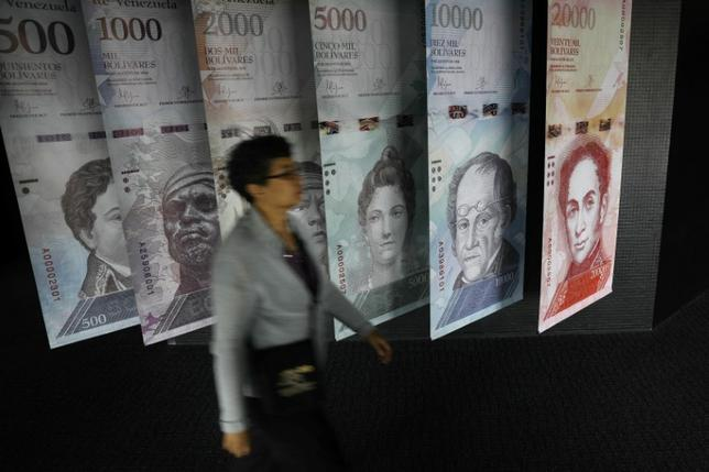 A woman walks by banners of Venezuelan bolivar notes displayed at the Venezuelan Central Bank building in Caracas, Venezuela May 23, 2017. REUTERS/Carlos Barria