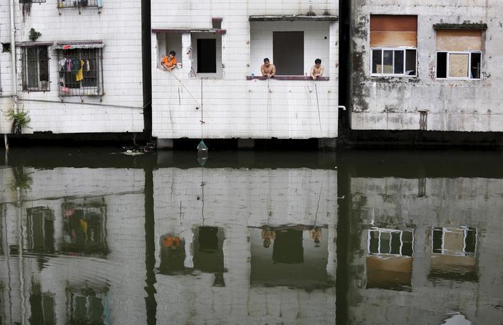People fish at an abandoned flat in Xian village, a slum area in downtown Guangzhou, China July 24, 2015. REUTERS/Tyrone Siu/Files