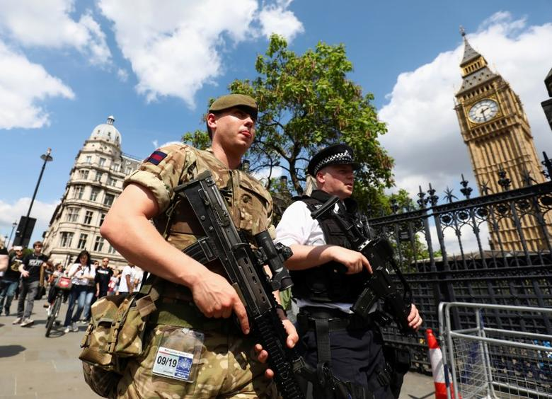 A soldier and police officer walk past the Houses of Parliament London, Britain May 24, 2017. REUTERS/Neil Hall