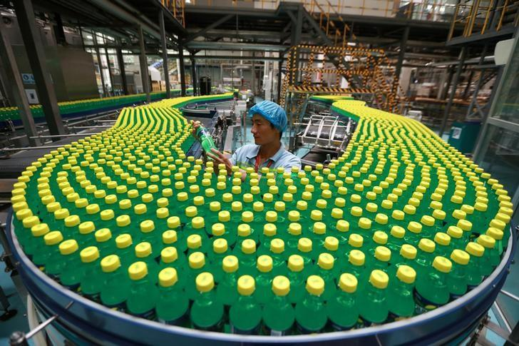 An employee checks on a drink bottle at a production line of a factory in Luohe, Henan Province, China, August 15, 2016. Picture taken August 15, 2016. REUTERS/Sheng Li