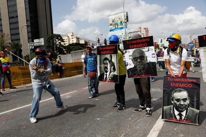 Demonstrators carry signs with images of President Nicolas Maduro (L) and politician Jorge Rodriguez and judge Maikol Moreno (R) that reads ''your real enemy'' while rallying against President Nicolas Maduro in Caracas, Venezuela, May 27, 2017. REUTERS/Carlos Garcia Rawlins