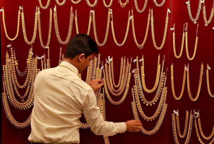 A salesman arranges gold ornaments, on a display board, inside a jewellery showroom during Akshaya Tritiya, a major gold buying festival, in Kochi, India April 28, 2017. REUTERS/Sivaram V