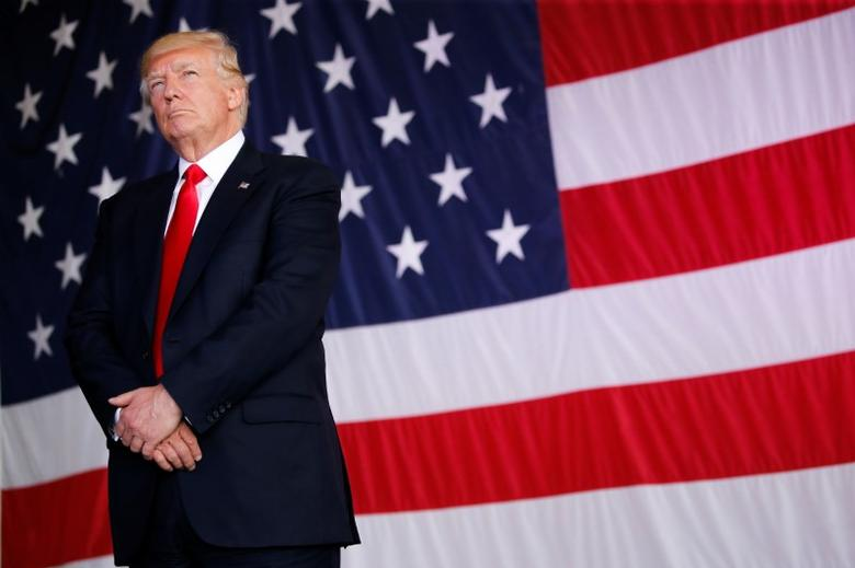 U.S. President Donald Trump stands in front of a U.S. flag while listening to U.S. first lady Melania Trump give a speech to U.S. troops at the Naval Air Station Sigonella before returning to Washington D.C. at Sigonella Air Force Base in Sigonella, Sicily, Italy, May 27, 2017REUTERS/Jonathan Ernst