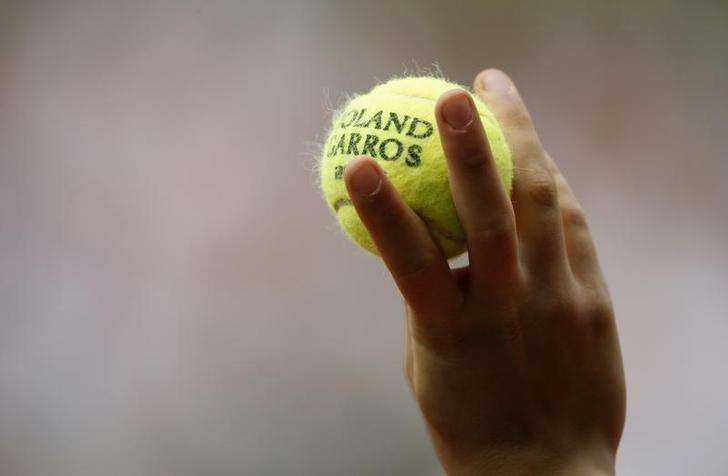 A ball boy holds up a ball during the match between Switzerland's Stanislas Wawrinka and Chile's Fernando Gonzalez at the French Open tennis tournament at Roland Garros in Paris May 31, 2008. REUTERS/Vincent Kessler/Files