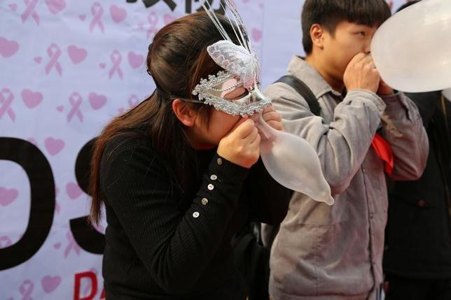 5月29日、中国の若者世代は、保守的な親世代よりもずっとセックスについてオープンな意識を持ち、性感染症対策の必要性についての認識も急速に広まっている。写真は2016年11月、重慶市で開かれたAIDS啓発イベントで、コンドームを膨らませる参加者(2017年 ロイター)