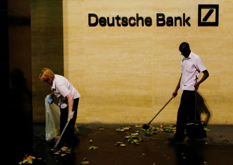 FILE PHOTO: Workers sweep leaves outside Deutsche Bank offices in London. REUTERS/Luke MacGregor/File Photo