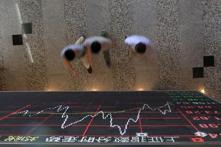 资料图片:2015年9月,中国上海,人们走过上海证交所显示股票信息的电子屏下方。REUTERS/Aly Song