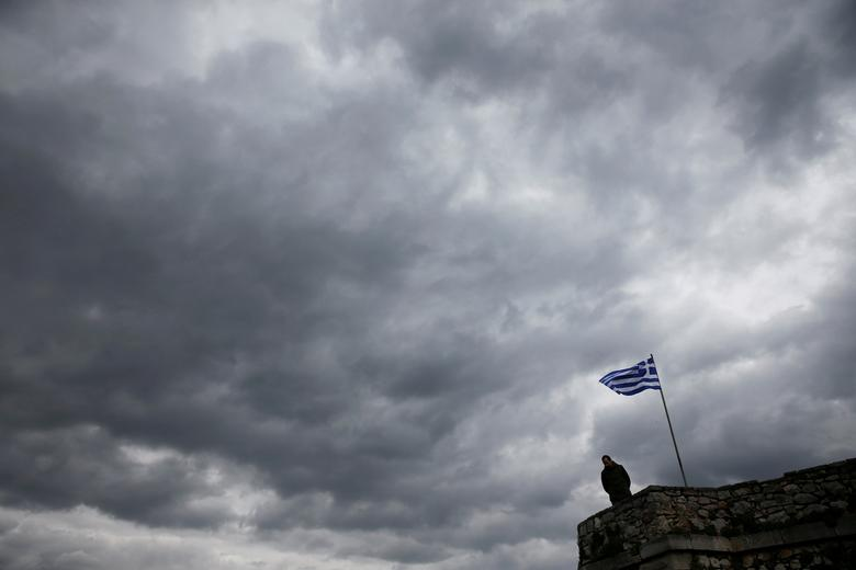 FILE PHOTO: A man looks down as a Greek national flag flutters atop one of the bastions of the 17th century fortress of Palamidi under an overcast sky at the southern port city of Nafplio, Greece, February 19. 2017. REUTERS/Alkis Konstantinidis/File Photo