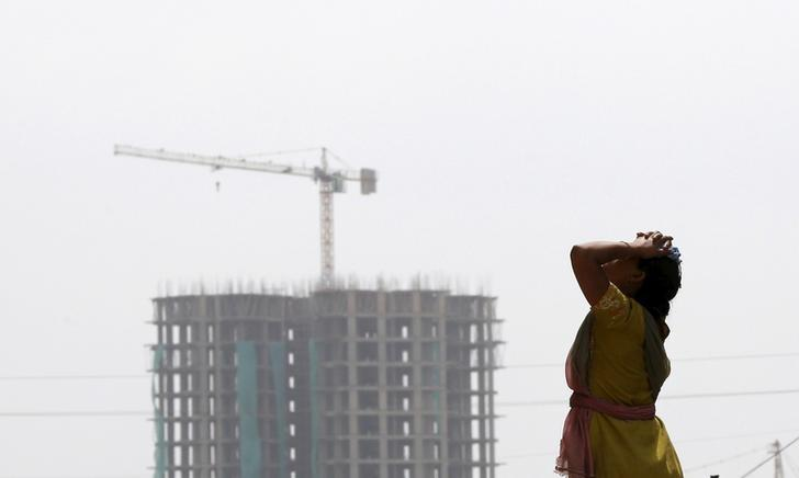 A labourer takes a break from her work at the construction site of a residential complex in Noida on the outskirts of New Delhi, August 20, 2015. REUTERS/Adnan Abidi/Files