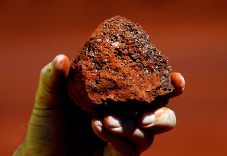 A miner holds a lump of iron ore at a mine located in the Pilbara region of Western Australia, December 2, 2013.   REUTERS/David Gray/File photo