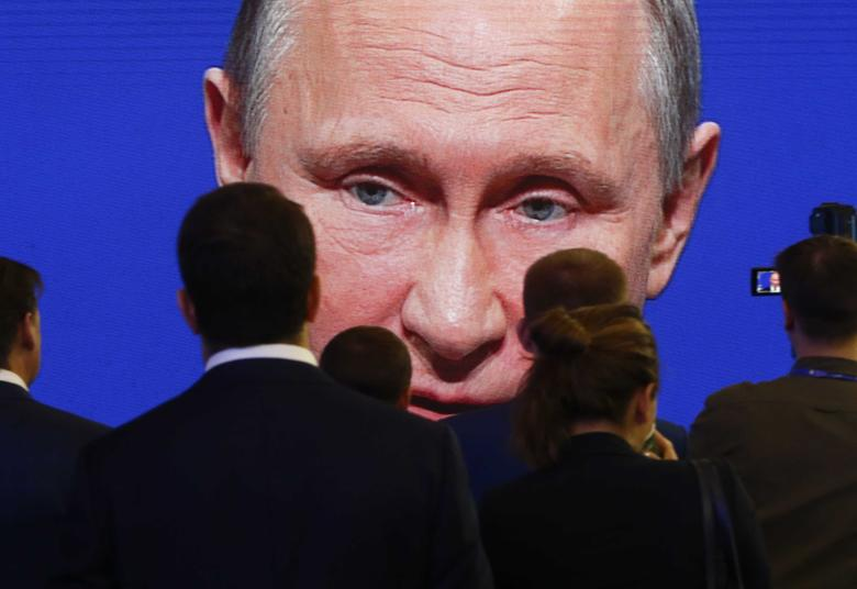 Participants of the St. Petersburg International Economic Forum (SPIEF) gather near an electronic screen showing Russian President Vladimir Putin, who speaks during a session of the forum in St. Petersburg, Russia, June 2, 2017. REUTERS/Sergei Karpukhin